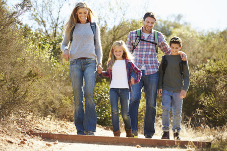 man outdoors: Family Hiking In Countryside Wearing Backpacks