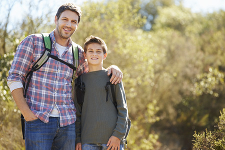 Father And Son Hiking In Countryside Wearing Backpacks Stock Photo