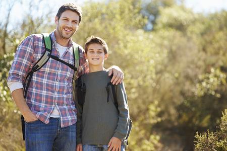 Vader en Zoon Wandelen In Platteland Dragen Rugzakken Stockfoto