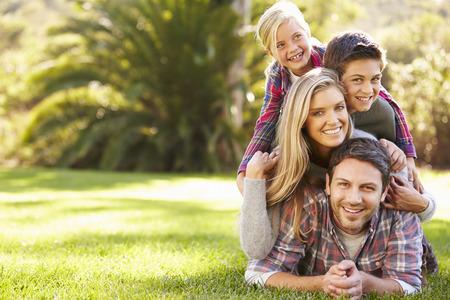 田舎の草の上に横たわる家族の肖像