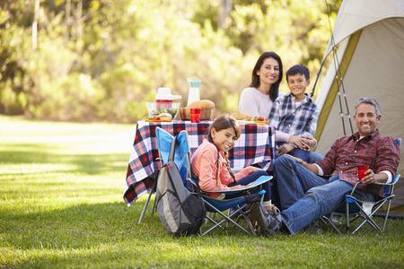 Família que aprecia o feriado de acampamento No Campo