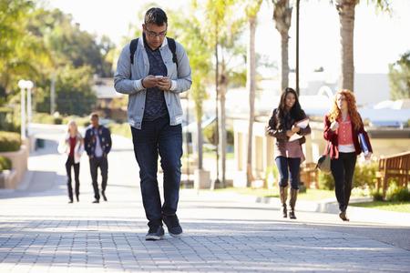 university text: Students Walking Outdoors On University Campus