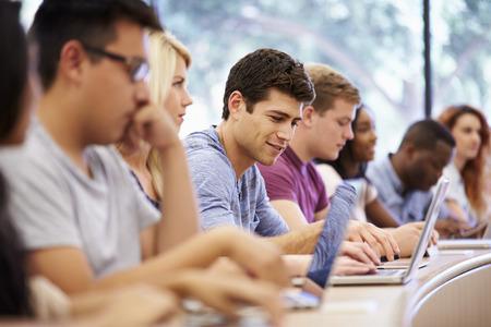Clase de los estudiantes universitarios usan las computadoras portátiles en clase