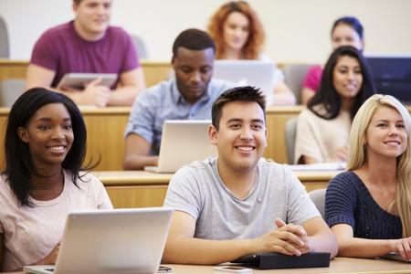 estudiantes universitarios: Estudiantes que usan las computadoras portátiles y tabletas digitales en Conferencia Foto de archivo