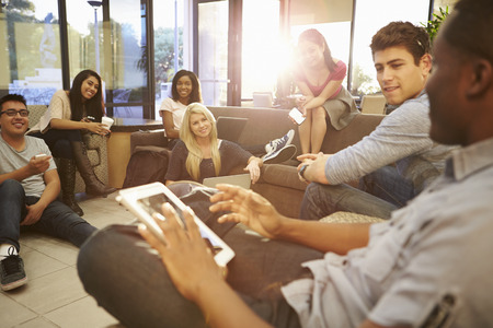 personas platicando: Grupo de estudiantes universitarios que se relajan en sala común