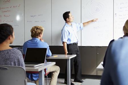 high school teacher: Tutor With High School Students In Class Using Laptops