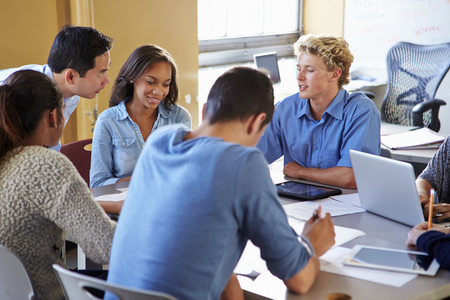 collaborating: High School Students With Teacher In Class Using Laptops