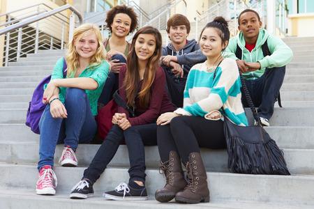 Retrato de estudiantes de secundaria que se sienta fuera del edificio