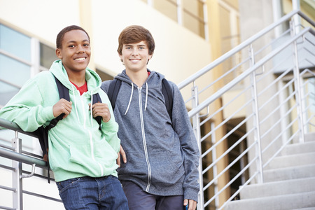 secondary school: Two Male High School Students Standing Outside Building Stock Photo