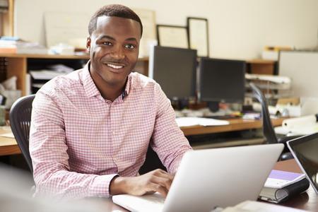 남성 설계자는 노트북에서 책상에서 일하고