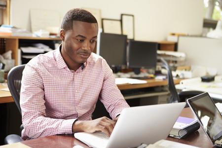 hombres trabajando: Arquitecto de sexo masculino Trabaja En El Escritorio En La Computadora Portátil Foto de archivo