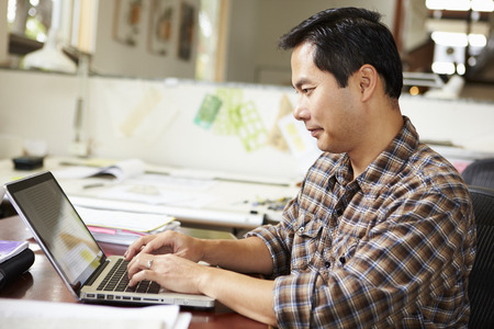 asian architect: Male Architect Working At Desk On Laptop