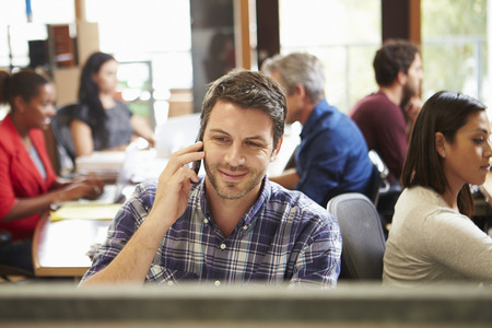 Male Architect Working At Desk With Meeting In Background photo