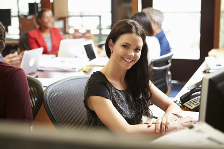Businesswoman Working At Desk With Meeting In Background photo