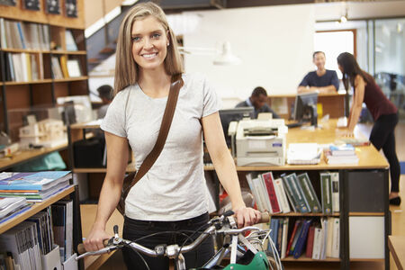 Architect Arrives At Work On Bike Pushing It Through Office photo