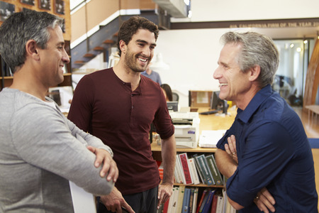 group plan: Three Male Architects Chatting In Modern Office Together Stock Photo