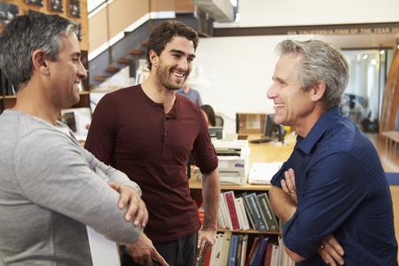 personas platicando: Tres Arquitectos masculinos que charlan en la oficina moderna Juntos