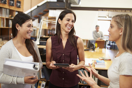 Three Female Architects Chatting In Modern Office Together photo