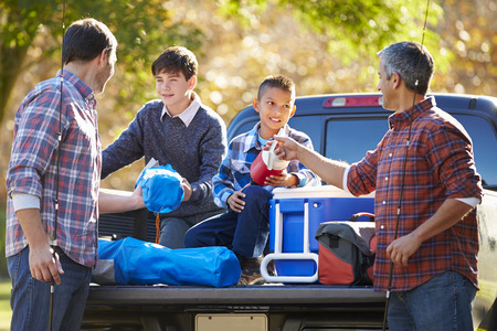 Fathers With Sons Unpacking Truck On Camping Holiday photo