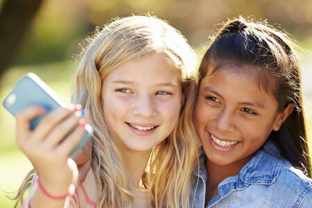 11 years: Two Girls Taking Selfie With Mobile Phone