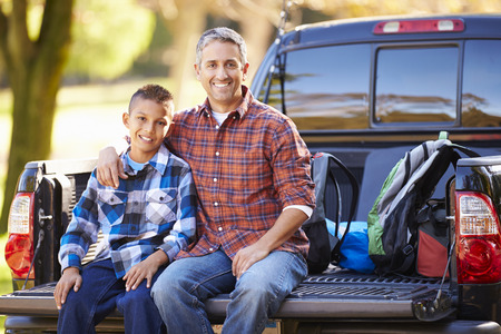 Father And Son Sitting In Pick Up Truck On Camping Holiday photo