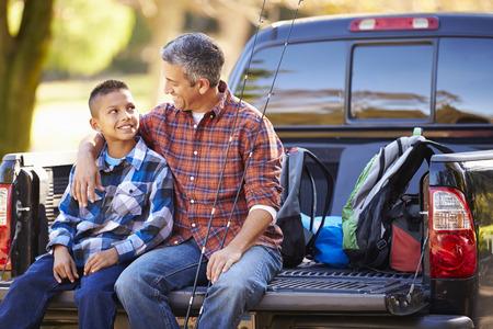 camioneta pick up: Padre e hijo se sienta en Camioneta Pickup en acampada