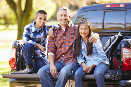 Father And Children Sitting In Truck On Camping Holiday photo