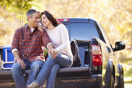 Couple Sitting In Pick Up Truck On Camping Holiday photo