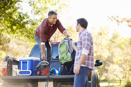 camping equipment: Two Men Unpacking Pick Up Truck On Camping Holiday