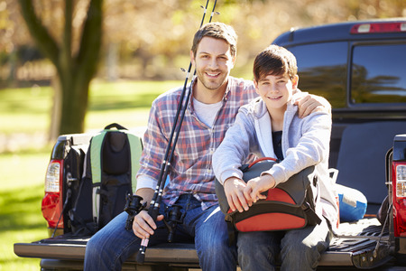 man fishing: Father And Son Sitting In Pick Up Truck On Camping Holiday