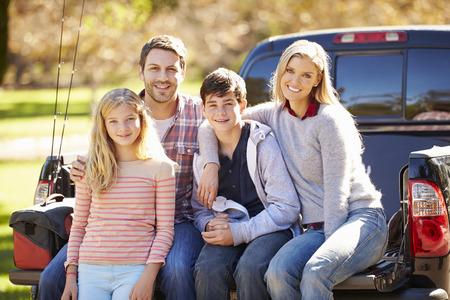 Familia que se sienta en Pick Up Camión en acampada Foto de archivo
