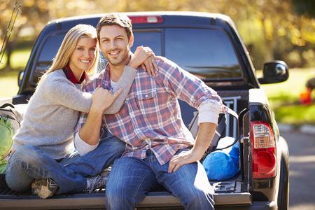 Pareja sentada en la Pick Up Camión en acampada