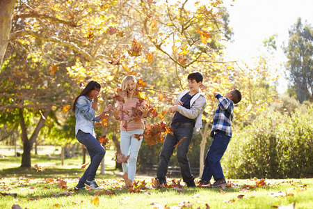 10 to 12 years old: Four Children Throwing Autumn Leaves In The Air Stock Photo