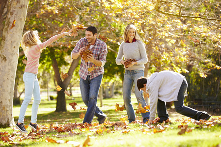 hojas antiguas: Familia que lanzan las hojas de oto�o en el aire Foto de archivo