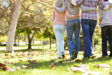 Rear View Of Family Walking Through Autumn Woodland