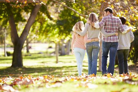 ni�os caminando: Vista posterior de la familia que recorre a trav�s del arbolado del oto�o Foto de archivo