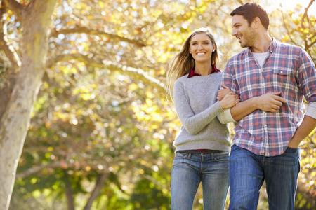 Pares románticos que recorren a través del arbolado del otoño