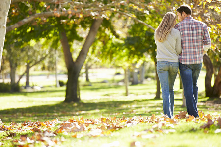 가을 숲을 걷는 로맨틱 커플의 후면보기
