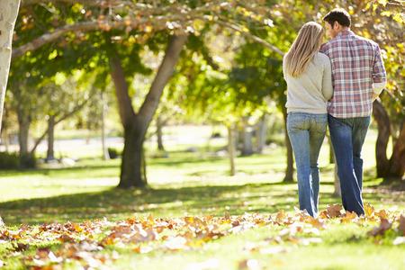 parejas felices: Vista posterior de los pares rom�nticos que recorren a trav�s del arbolado del oto�o Foto de archivo