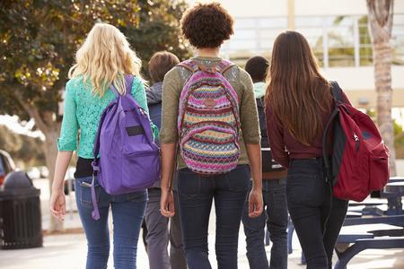 Vista posterior de los estudiantes que caminan a la escuela secundaria
