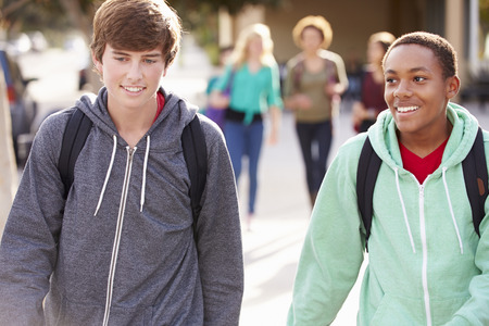 highschool students: Two Male Students Walking To High School