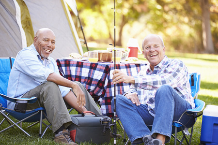 resting rod fishing: Two Senior Men On Camping Holiday With Fishing Rod Stock Photo