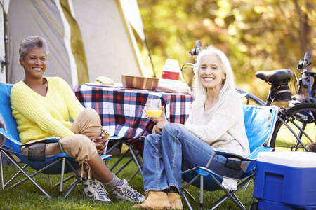 mature women: Two Mature Women Relaxing On Camping Holiday Stock Photo