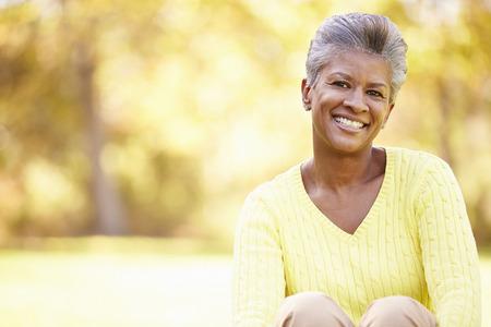 sorrisos: Mulher madura que relaxa na paisagem do outono