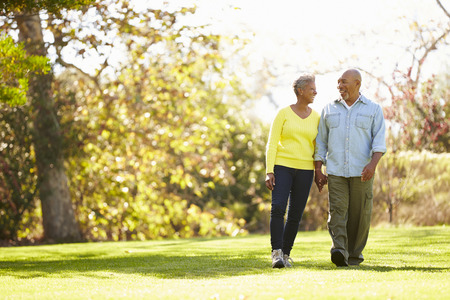 pärchen: Ältere Paare, die durch Herbst-Waldland Lizenzfreie Bilder