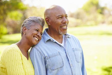 parejas caminando: Pares mayores que recorren a través del arbolado del otoño