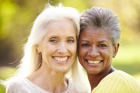 Portrait Of Two Mature Female Friends Hugging Banco de Imagens