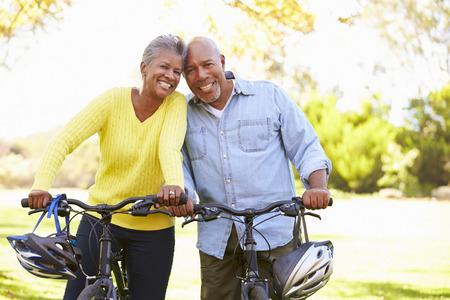 riding helmet: Pares mayores en paseo del ciclo En Campo Foto de archivo