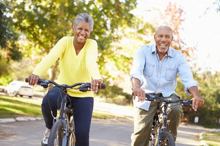 andando en bicicleta: Pareja mayor en paseo del ciclo En Campo