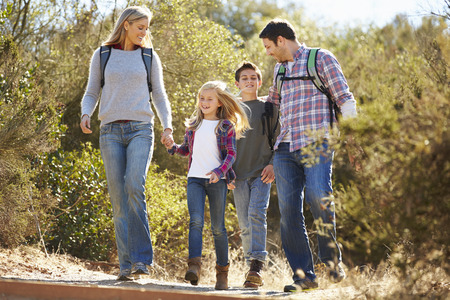 8 10 years: Family Hiking In Countryside Wearing Backpacks